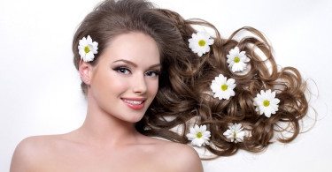 Smiling woman with beautiful long hair wna flowers in it - white background